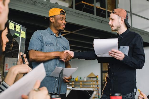 Творческие африканские и кавказские молодые люди, рукопожатие во время рабочей встречи в офисе. работа в команде, офис, it, фриланс