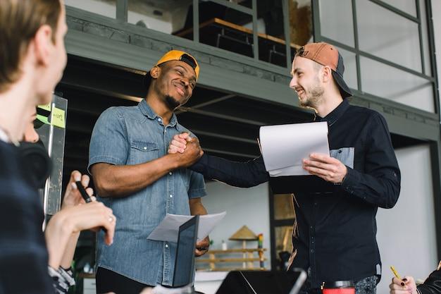 オフィスでの作業会議中に握手する創造的なアフリカと白人の若い男性。チームワーク、オフィス、it、フリーランス