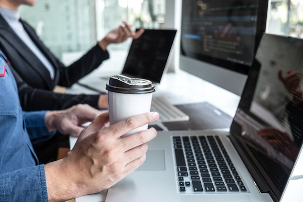 It会社のオフィスのソフトウェア開発コンピューターでプロジェクトに取り組んでいるプログラマーのプロフェッショナルチーム