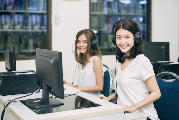 女子学生がitルームで勉強しながらコンピューターでポーズします。