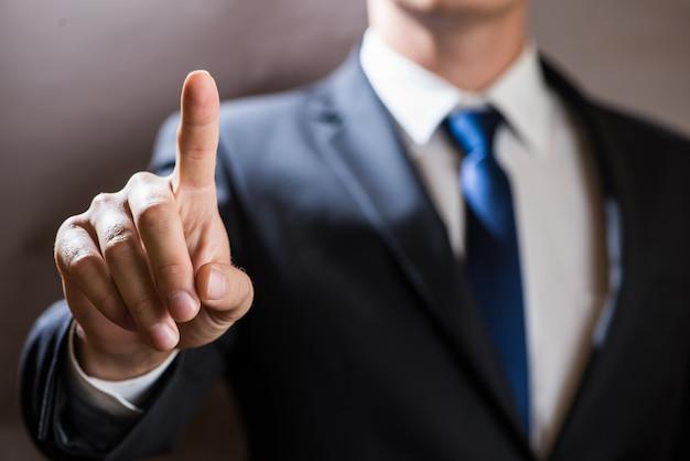 ビジネスマンは仮想タッチスクリーンをクリックします。未来的なitプレゼンテーションの背景