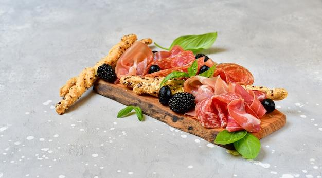 Итальянская закуска с ветчиной, салями, помидоры с оливками брезаола и хлебные палочки гриссини. аперитив счастливый час