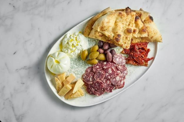 Итальянские закуски антипасти на белой тарелке на мраморе