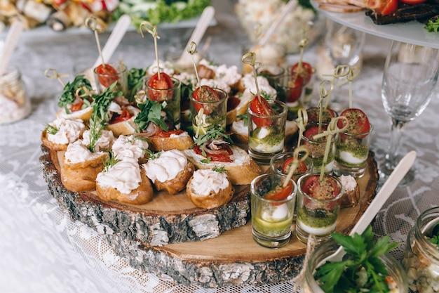 イタリアの前菜ワインスナックセットbrushettasチーズの品種地中海オリーブピクルスプロシュートディパルマメロンサラミと黒グランジの背景の上面図上のグラスワイン