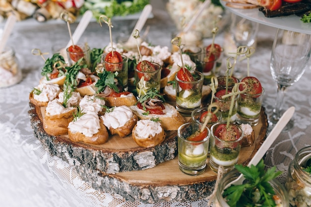 Italian antipasti wine snacks set brushettas cheese variety mediterranean olives pickles prosciutto di parma with melon salami and wine in glasses over black grunge background top view