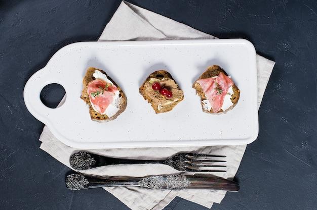 Italian antipasti with pate, parma and salami on toast.