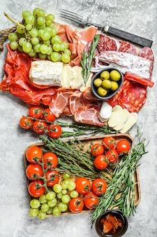 Italian antipasto, wooden cutting board with prosciutto