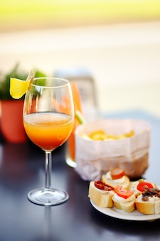 Italian aperitives/aperitif: glass of cocktail (sparkling wine with aperol) and appetizer platter on the table