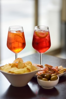 Italian aperitives/aperitif: glass of cocktail (sparkling wine with aperol) and appetizer platter on the table.