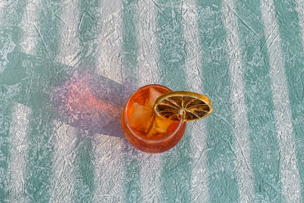 Italian aperol spritz alcohol cocktail with ice cubes and dried orange slice
