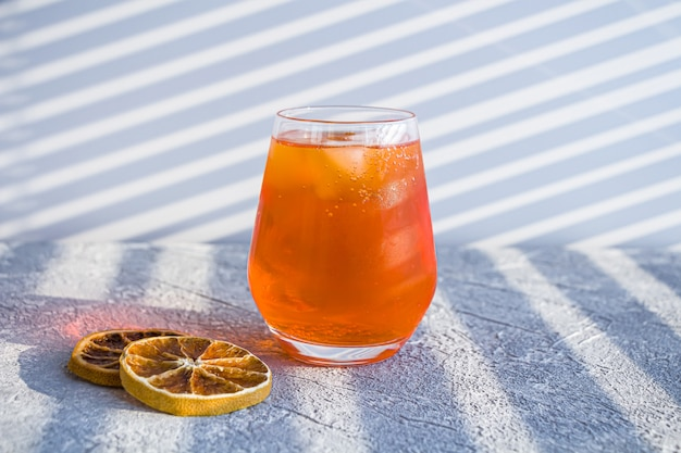Italian aperol spritz alcohol cocktail with ice cubes and dried orange slices