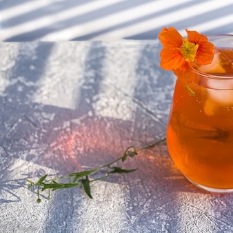 Italian aperol spritz alcohol cocktail with ice cubes and flower