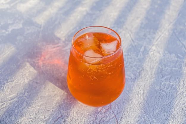 Итальянский алкогольный коктейль aperol spritz с кубиками льда. летний освежающий апельсиновый напиток с горьким игристым вином просекко и содовой.