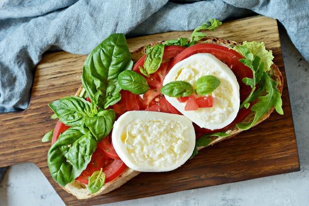 파란색 배경에 나무 판자에 카프레제 샐러드를 곁들인 이탈리아 전채 브루스케타 토스트