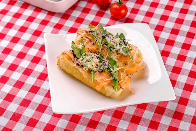 Итальянская закуска брускетта с лососем, пармезаном, бальзамическим уксусом и свежей рукколой на белой тарелке
