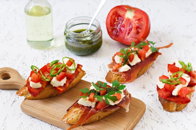 Italian appetizer - bruschetta with tomatoes, chili, sausage and cheese on a wooden board