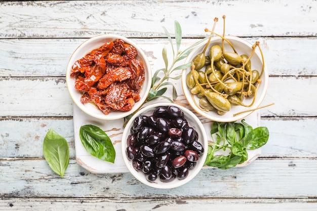 上からのイタリアの前菜。地中海のスナックの品揃え。ブラックオリーブ、ケーパー、オリーブオイル、サンドライトマトの上面図。