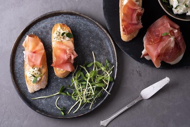 Итальянская закуска из хлеба и прошутто, кростини с ветчиной, рикоттой и микрозеленью на сером фоне, закуски.