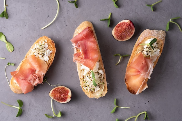 Italian appetizer toast with prosciutto, cheese and microgreens on gray concrete background, close-up.