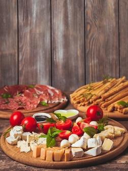 Итальянская закуска - различные виды ветчины, сыра и гриссини с копией пространства на стене