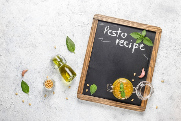 Italian basil pesto sauce with culinary ingredients for cooking.