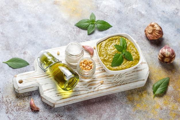 Итальянский соус песто из базилика с кулинарными ингредиентами для приготовления.