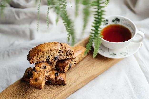 軽いテーブルクロスの上に紅茶のカップとイタリアのビスコッティクッキー。居心地の良い写真の上面図