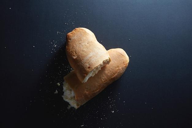Italian bread in half the broken isolated on black
