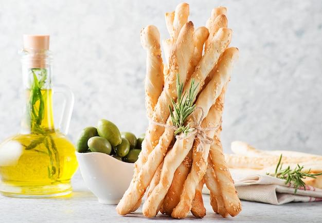밝은 배경, 선택적 초점, 수평 방향에 참깨와 허브를 넣은 이탈리아 빵