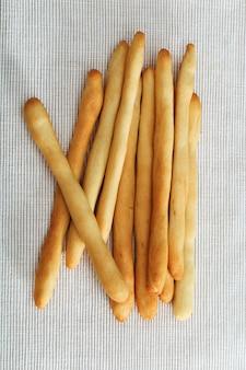 Italian breadsticks on light fabric.