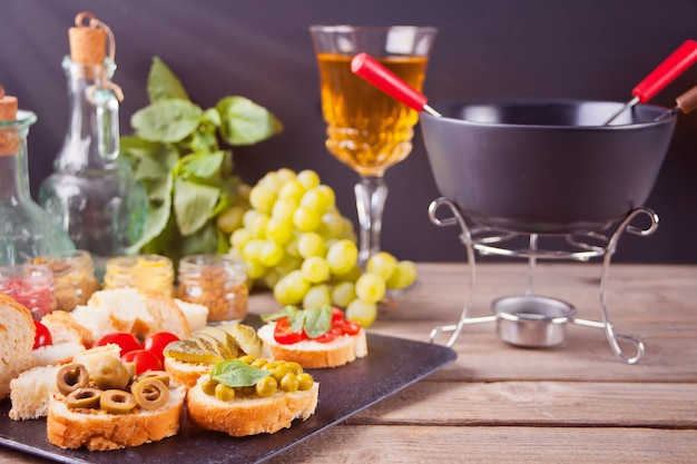 Italian bruschetta in assortment on the plate, glasses with white wine, grapes, fondue. party or dinner concept.