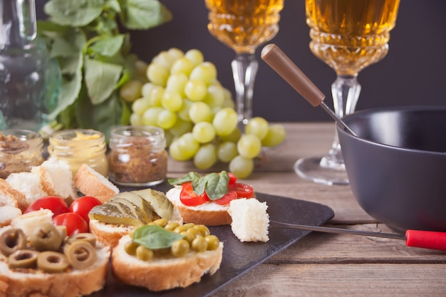 Italian bruschetta in assortment on the plate, glasses with white wine, grapes, fondue.
