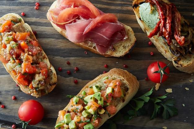 Итальянская брускетта с жареными помидорами, авокадо, лососем, ветчиной, перцем, зеленью на деревянной доске