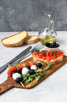 Italian bruschetta with tomatoes, olive oil, green parsley and pink pepper.