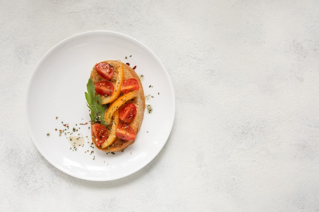 Italian bruschetta with tomatoes on a white plate against white background. view from above