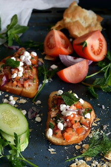 Italian bruschetta with vegetable salsa on a dark background
