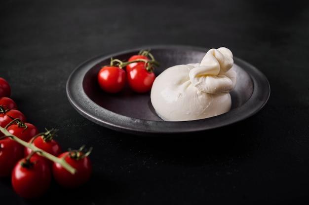 Итальянский сыр буррата и ветка помидоров черри на темной тарелке выборочный фокус крупным планом низкий ключ