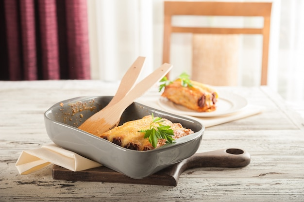 Итальянская паста каннеллони на светлом столе. плоско заложить пасту канелони крупным планом на ужин и скопировать пространство.