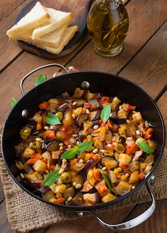Italian caponata with frying pan on a wooden table
