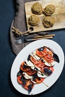 Italian caprese salad.ingredients mozzarella cheese, tomatoes, basil, salt, pepper, balsamic.