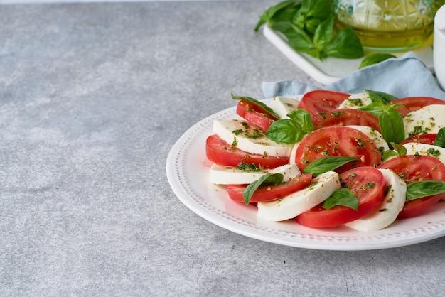 イタリアのカプレーゼサラダは、地中海料理のデトックス健康的な前菜のコピースペースの側面図を提供しました