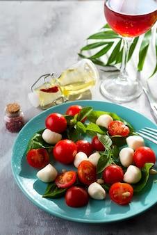 Italian caprese salad with red tomatoes, fresh organic mozzarella and basil on stone table