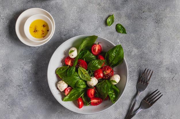 회색 배경에 슬라이스 토마토, 모짜렐라, 바질, 올리브 오일과 함께 이탈리아 카프레제 샐러드