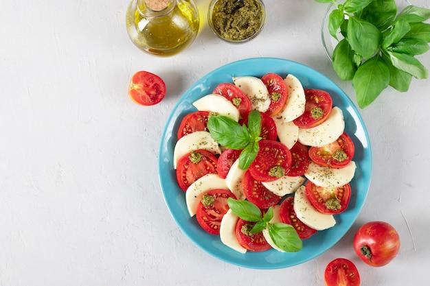 Итальянский салат капрезе с нарезанными помидорами, сыром моцарелла, базиликом и оливковым маслом на синей тарелке на светло-сером фоне. копировать пространство