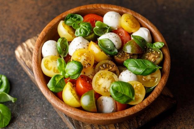スライスしたトマト、モッツァレラチーズ、バジル、オリーブオイルを木製のボウルに入れたイタリアンカプレーゼサラダ。