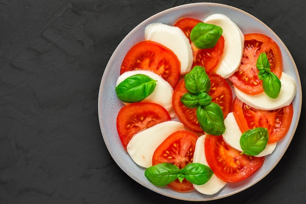 Italian caprese salad with sliced tomatoes, mozzarella cheese, basil, olive oil in a plate