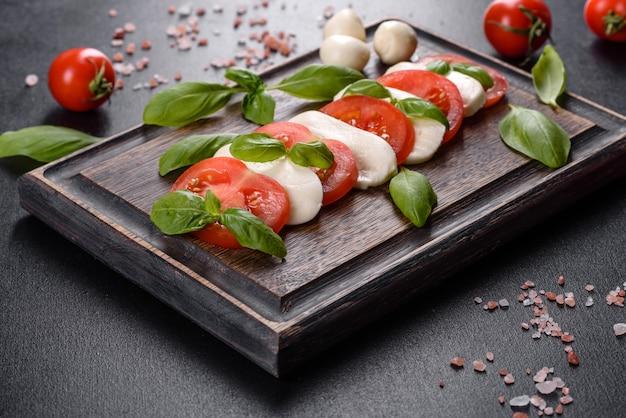 スライストマト、モッツァレラチーズ、バジル、オリーブオイルのイタリアンカプレーゼサラダ。暗いコンクリートの背景にヴィンテージの黒いプレートで提供