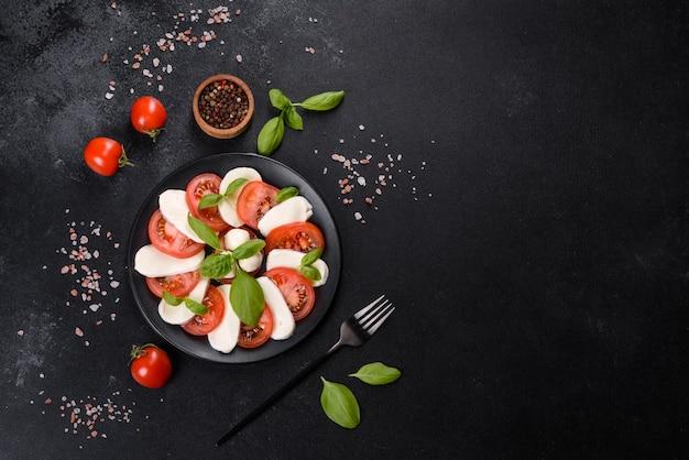 Итальянский салат капрезе с нарезанными помидорами, сыром моцарелла, базиликом, оливковым маслом. подается в винтажной черной тарелке на темном бетонном фоне.