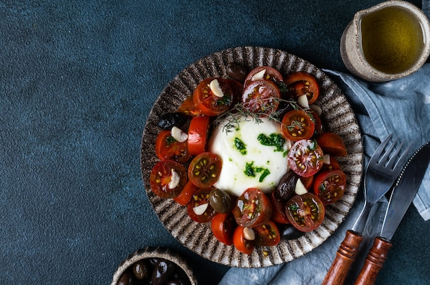 Italian caprese salad with sliced tomatoes, mozzarella cheese, olive oil on dark background. top view. black tomato salad with burrata and garlic. comfort food. sustainable consumption.