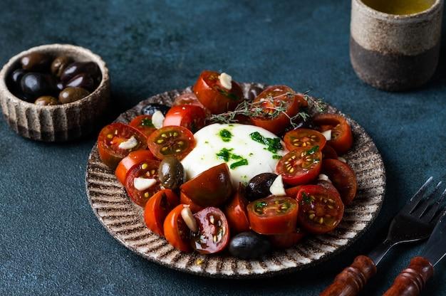 어두운 배경에 얇게 썬 토마토, 모짜렐라 치즈, 올리브 오일을 곁들인 이탈리아 카프레제 샐러드. 부라타와 마늘을 곁들인 블랙 토마토 샐러드. 컴포트 푸드. 지속 가능한 소비